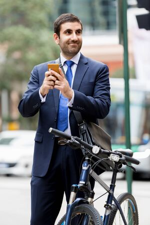 Young businessman with bike holding mobile phone