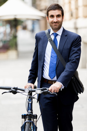 Young businessman with bike outdoors Stock Photo