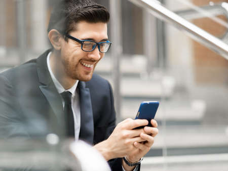 Portrait of young handsome businessman outdoor holding mobile phone Stock Photo