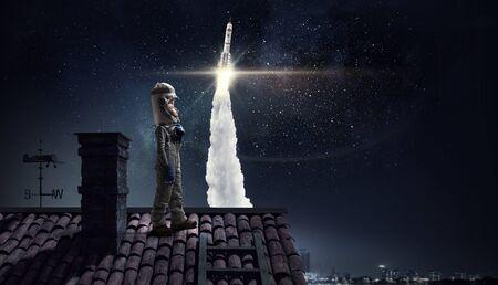 anochecer: La muchacha divertida en traje espacio en tejado de la casa soñando que es astronauta