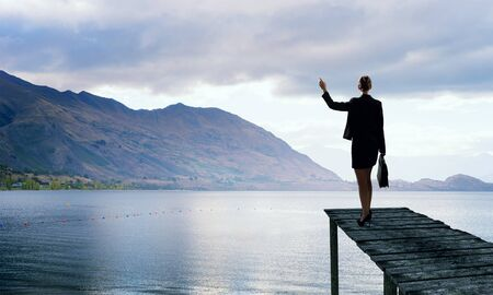 Back view of businesswoman standing on bay and viewing lake