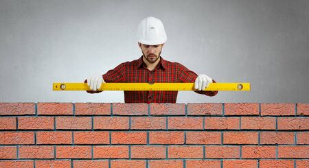 journeyman: Bricklayer using level to check new red brick wall outdoor
