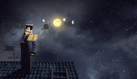 Funny boy in carton helmet reading book and dreaming he is astronaut