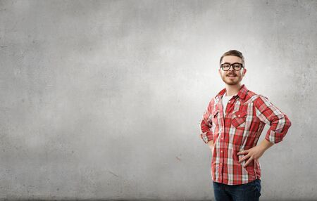 checked shirt: Man in checked shirt and eyeglasses against gray background