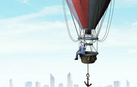 Businessman flying in aerostat high in sky Stock Photo
