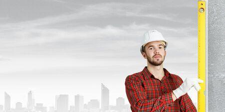 Engineer man in helmet outdoor using level