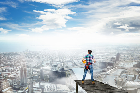 Back view of engineer man standing on bay and viewing city Stock Photo