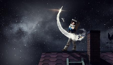 La muchacha divertida en traje espacio en tejado de la casa soñando que es astronauta