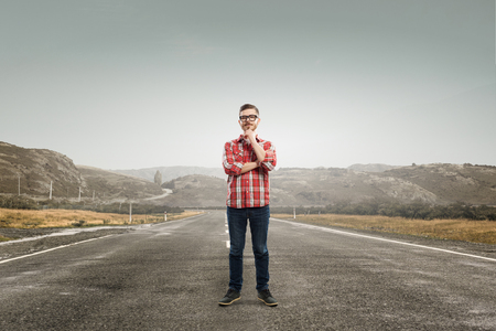 checked shirt: Pensive young man in checked shirt standing on road Stock Photo