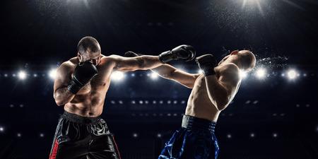 Dos boxeadores profesionales que luchan en la arena en los proyectores