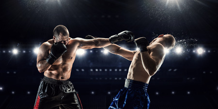 concentration: Two professional boxers fighting on arena in spotlights