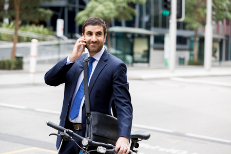 Young businessman with bike in city centre