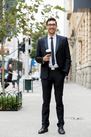 Portrait of young handsome businessman outdoor with cup Stock Photo