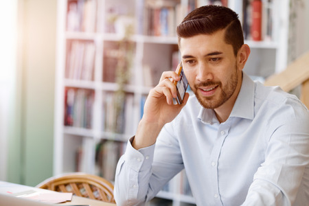Young businessman sitting in office and holding mobile phone Stock Photo