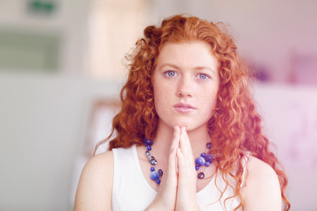 red head woman: Closeup portrait of a young red head woman praying