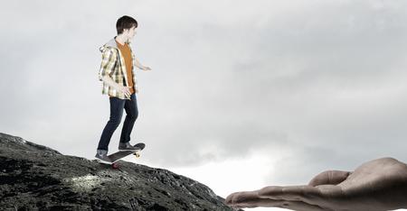 Teenager guy riding skateboard on rock edge