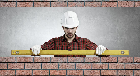 bricklayer: Bricklayer using level to check new red brick wall outdoor