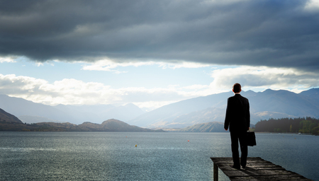 Back view of businessman standing on bay and viewing lake