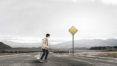 Teenager guy riding skateboard on asphalt road