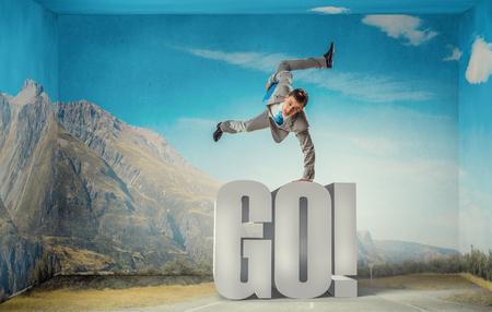 go go dancer: Active businessman making handstand on word go Stock Photo