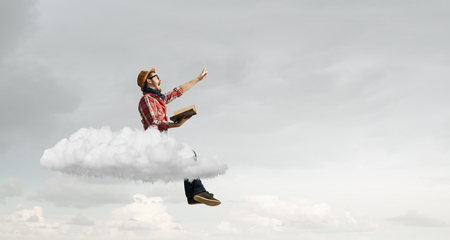 Hipster guy with book in hands on cloud in sky