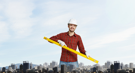 mixed media: Young handsome man in hardhat with measure level . Mixed media
