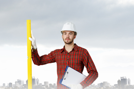 journeyman: Young handsome man in hardhat with measure level . Mixed media