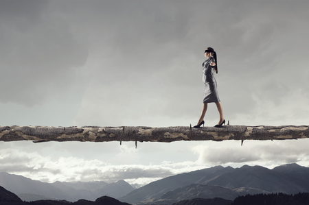 impediment: Blind businesswoman walking on wooden log above gap. Risk and challenge concept . Mixed media