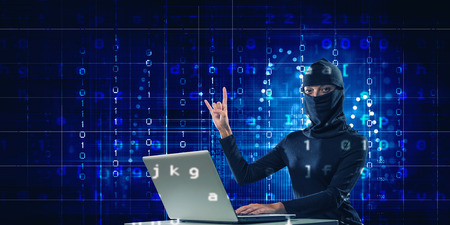 Woman hacker in mask using laptop against dark background . Mixed media Stock Photo