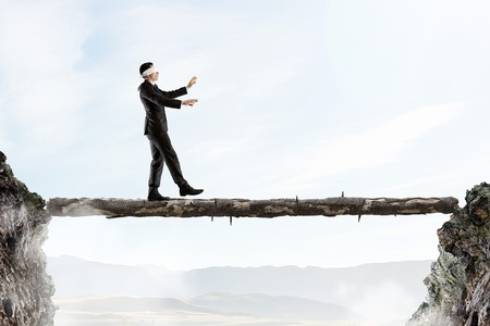 Blind businessman walking on log over gap. Risk and challenge concept . Mixed media Stock Photo