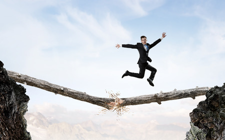 business obstacle: Young successful businessman jumping over gap. Risk and challenge concept . Mixed media Stock Photo