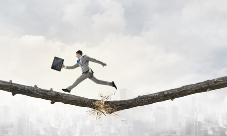 impediment: Young successful businessman jumping over gap. Risk and challenge concept . Mixed media Stock Photo