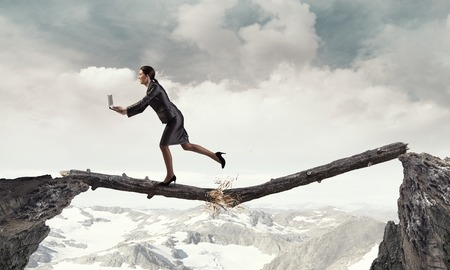 business obstacle: Young successful businesswoman jumping over gap. Risk and challenge concept . Mixed media Stock Photo