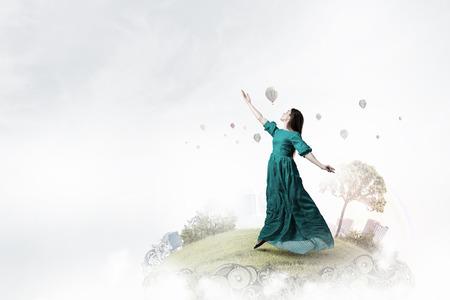 Dreamy beautiful woman in green dress flying in sky . Mixed media
