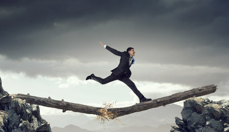 Young successful businessman jumping over gap. Risk and challenge concept . Mixed media Stock Photo