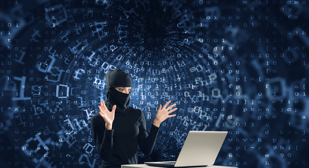 mugging: Woman hacker in mask using laptop against dark background . Mixed media Stock Photo