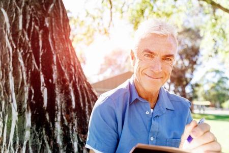 novel: Handsome senior sitting in park and reading book
