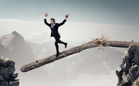 risky job: Young successful businessman jumping over gap. Risk and challenge concept