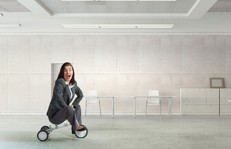 careless: Young careless businesswoman riding three wheeled bike in office. Mixed media