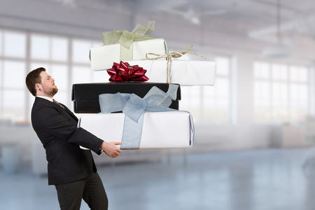 Young businessman in office with big gift boxes in hands. Mixed media