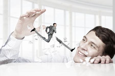 peep: Businessman peep from under table at running man. Mixed media