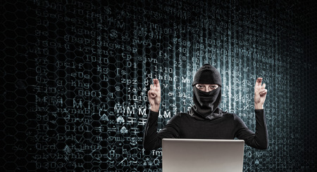mugging: Woman hacker in mask using laptop against dark background Stock Photo