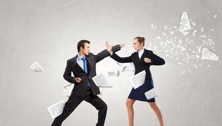 Aggressive businessman and businesswoman fighting each other