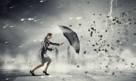 ヤングは強い風に逆らって歩く傘と実業家を決定