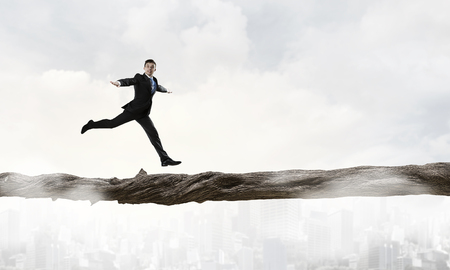 impediment: Young successful businessman running on log above gap. Risk and challenge concept