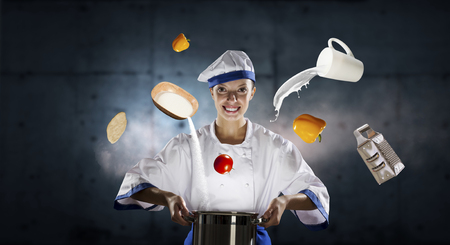 Young attractive cook woman making magic above pan