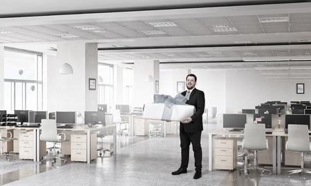 layoff: Young businessman in office with big gift boxes in hands. Mixed media