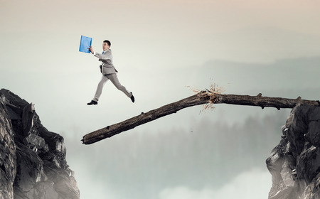 business obstacle: Young successful businessman jumping over gap. Risk and challenge concept