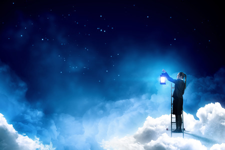 Young businesswoman in darkness with lantern in hand standing on ladder