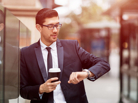 Portrait of young handsome businessman outdoor looking at his watch Stock Photo